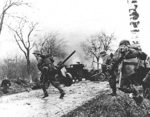 GERMAN_TROOPS_ADVANCING_PAST_ABANDONED_AMERICAN_EQUIPMENT